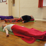 students lying in a yoga class
