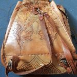 back of front of leather bag carved and painted with various designs