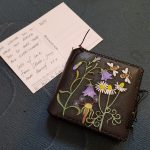 front of notebook with leather cover carved and painted with flowers