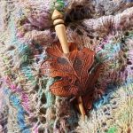 leather and wood shawl pin carved and painted to resemble an autumn leaf