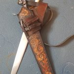 leather scabbard, this side carved and painted with flames, water, spirals and a rose